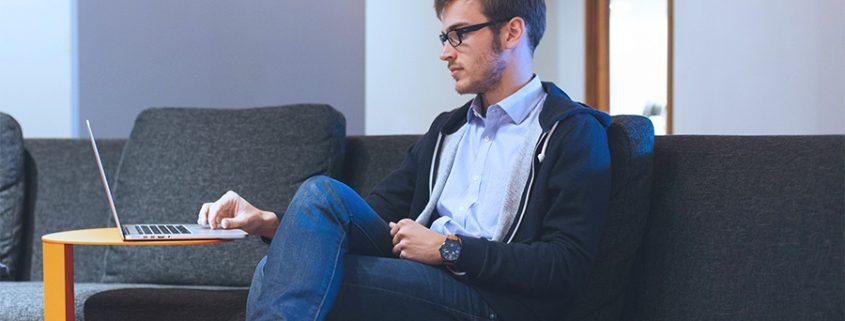 Homme assis sur un sofa utilisant son MacBook